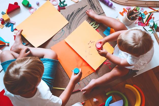 Crianças desenham e fazem artesanato crianças com brinquedos educativos e material escolar para a criatividade
