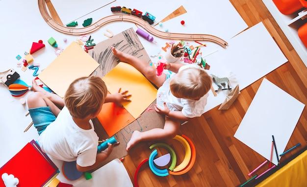 Crianças desenham e fazem artesanato infantil com brinquedos educativos na pré-escola e jardim de infância ou aulas de arte