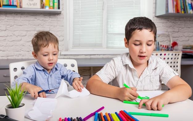 Crianças desenham juntas em casa, crianças pintam no jardim de infância
