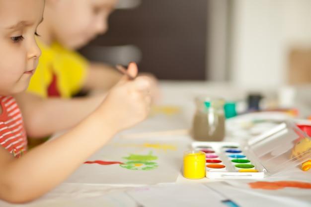 Crianças desenhando com tintas coloridas nos papéis.