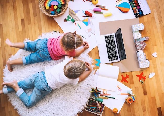 Crianças desenhando e fazendo artesanato com aulas de arte online em casa creche e tecnologia