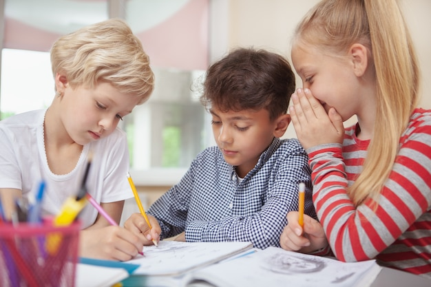 Crianças desenhando na aula de arte da escola primária