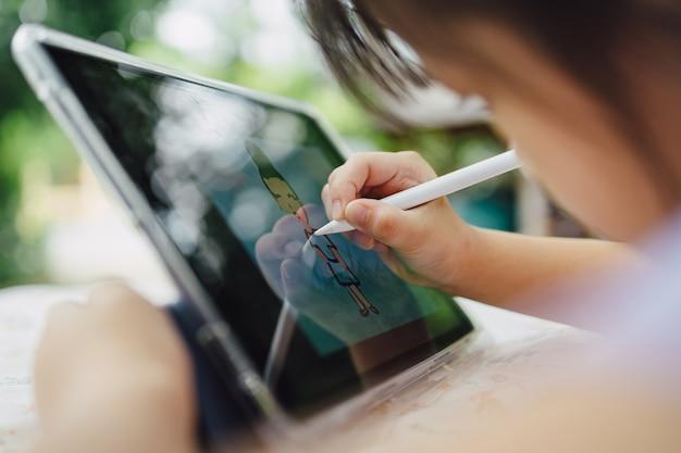 Crianças desenhando na tecnologia digital do tablet inteligente conceito para um novo estilo de normalidade de aprendizagem