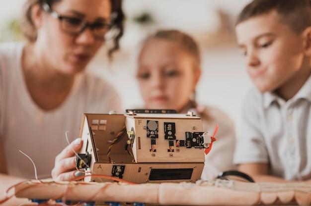 Crianças desfocadas e professor aprendendo uma aula de ciências
