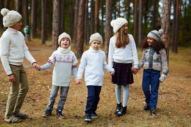 Crianças desfrutando de caminhada na floresta de outono