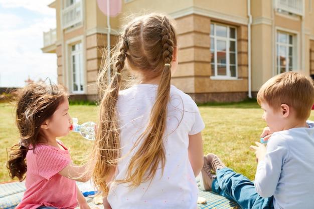 Crianças desfrutando de piquenique no gramado vista traseira