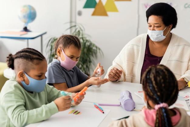 Crianças desinfetando as mãos na sala de aula
