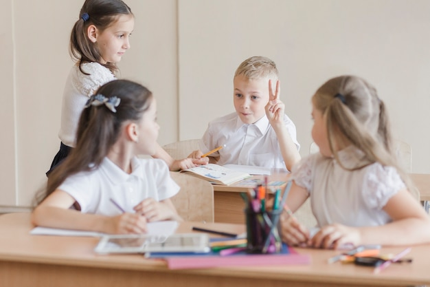 Crianças discutindo em mesas em sala de aula