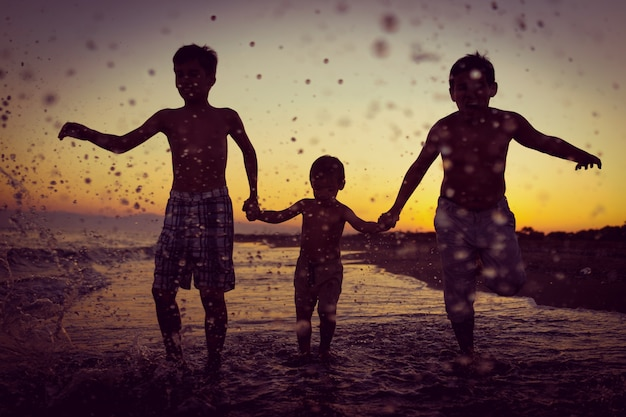 Crianças divertidas jogando splash na praia