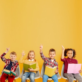 Crianças do espaço de cópia com os braços levantados para responder