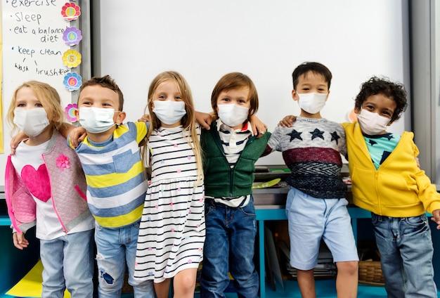 Crianças do jardim de infância usando máscaras em uma sala de aula