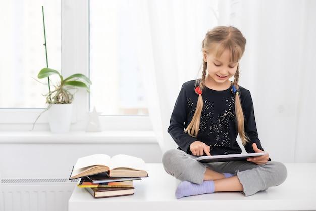 Crianças do sexo feminino sorrindo, usando o tablet digital, assistindo a um vídeo de e-learning on-line para estudar inglês em casa