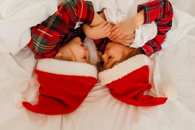 Crianças dormindo juntas no dia de natal
