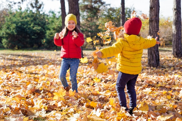 Crianças, duas lindas irmãs pequenas brincam com folhas amarelas no outono