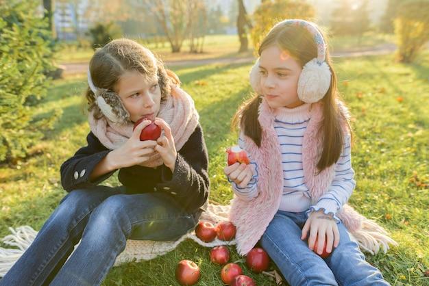 Crianças duas meninas comendo maçãs vermelhas no parque outono amarelo
