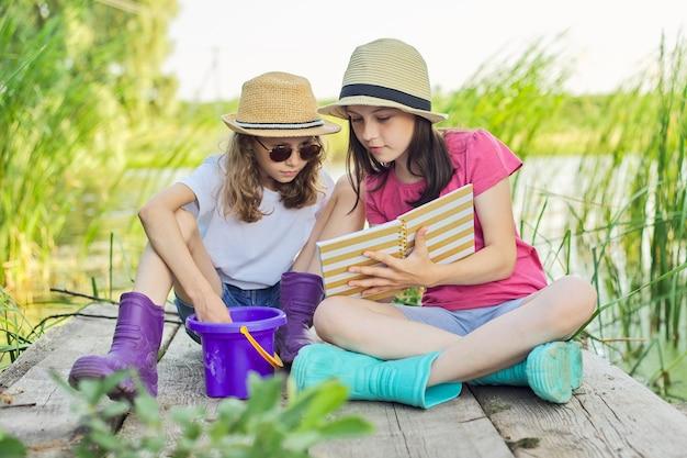 Crianças duas meninas descansando brincando lendo seu caderno na natureza. crianças sentadas no cais do lago de madeira, fundo de paisagem aquática do pôr do sol de verão, estilo country