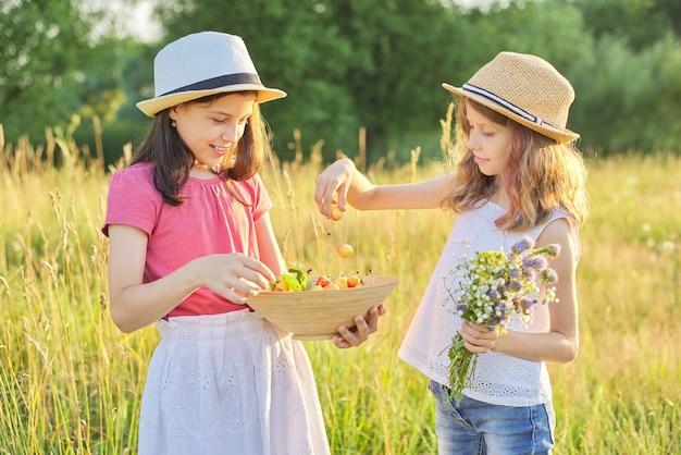Crianças, duas meninas em um dia ensolarado de verão em um prado com uma tigela de cereja doce, com o pôr do sol