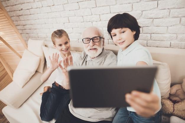 Crianças e avô fazem vídeo chamada com tablet.