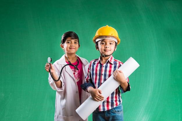 Crianças e conceito de educação - pequeno menino indiano e uma menina posando em frente ao quadro de giz verde em traje de gala de engenheiros e fantasia de médico com estetoscópio