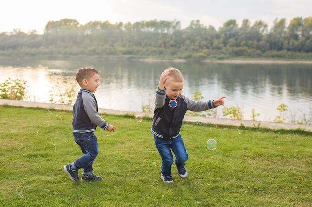 Crianças e conceito de infância - dois irmãos meninos brincando com bolhas de sabão coloridas