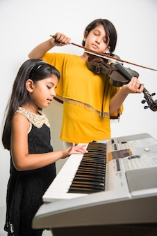 Crianças e conceito de música - garotinhas indianas tocando instrumentos musicais como piano, teclado ou violino