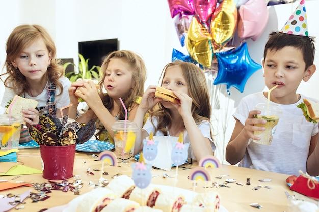 Crianças e decorações de aniversário. meninos e meninas na configuração da mesa com alimentos, bolos, bebidas e gadgets de festa.