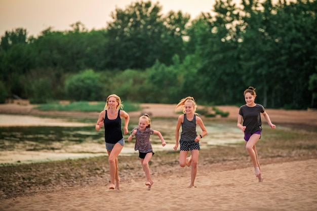 Crianças e meninas adultas correm ao longo da costa em roupas esportivas em um fundo de natureza ao pôr do sol