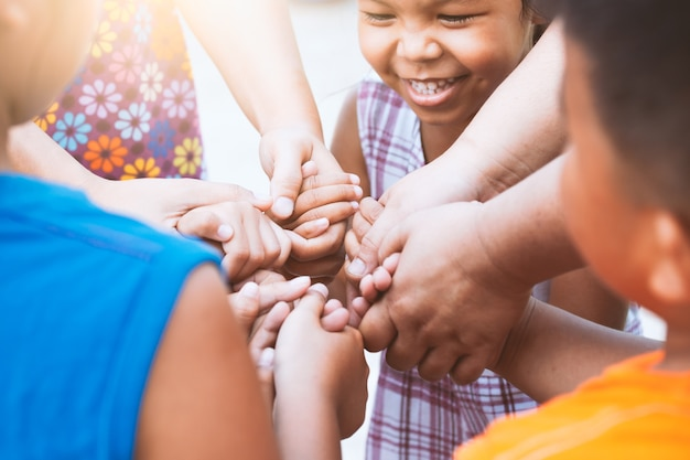 Crianças e pais de mãos dadas e jogando juntos com a unidade e trabalho em equipe