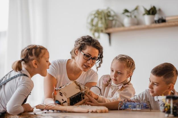 Crianças e professor aprendendo uma aula de ciências