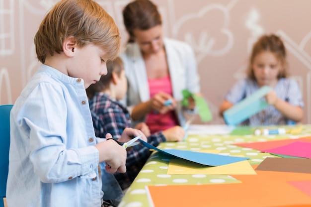 Crianças e professor cortando papel juntos