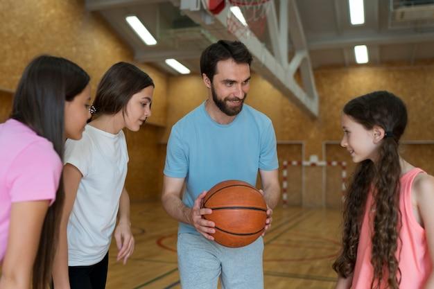 Crianças e professor de tiro médio com bola de basquete