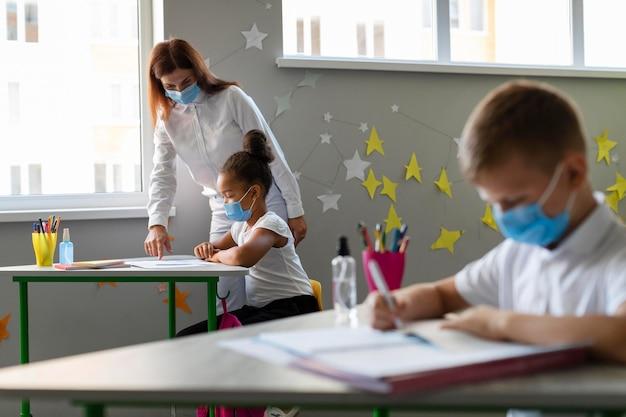 Crianças e professor usando máscaras médicas