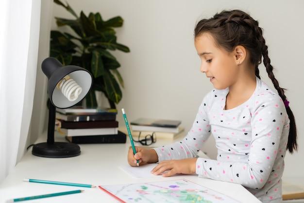 Crianças, educação e conceito de aprendizagem - aluna com livro escrevendo no caderno em casa