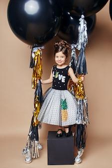 Crianças elegantes em vestidos de noite e trajes comemorando o primeiro dia de aula