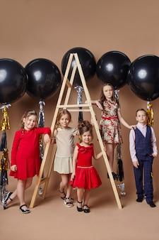 Crianças elegantes em vestidos de noite e trajes comemorando o primeiro dia de aula.