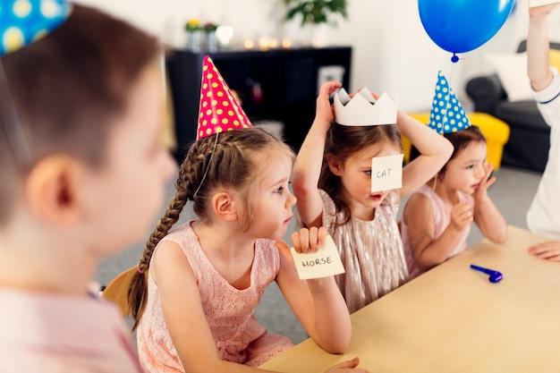 Crianças em bonés coloridos jogando