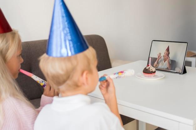 Crianças em casa em quarentena comemorando aniversário com tablet