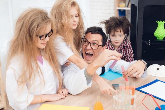 Crianças em casacos fazem experimentos químicos durante a aula.