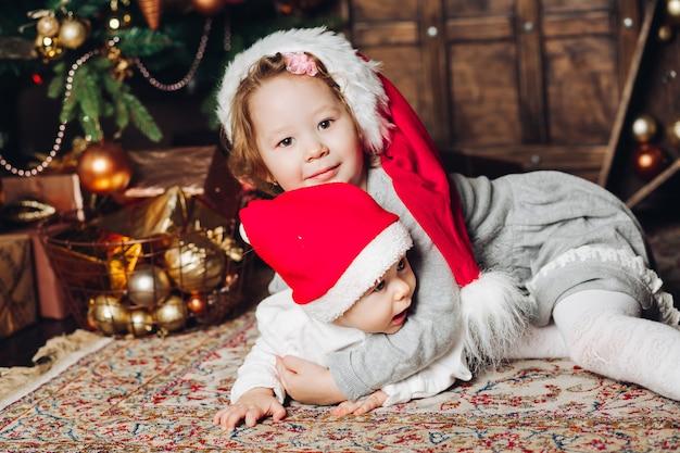 Crianças em chapéus de papai noel no tapete na árvore do abeto decorada.