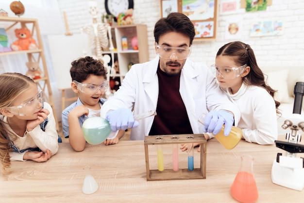 Crianças em conjunto com o professor para aulas de química.