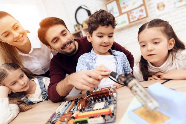 Crianças em conjunto com o professor trabalham com um ferro de solda.