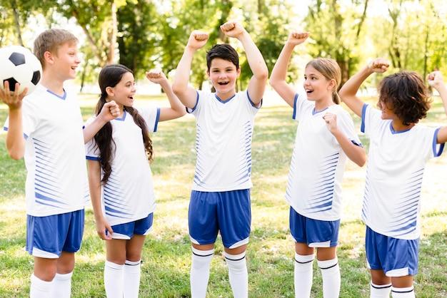 Crianças em equipamentos de futebol vitoriosas após uma partida