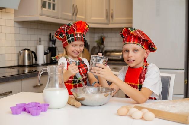 Crianças em fantasias de chef estão cozinhando biscoitos festivos no conceito de inverno de ano novo da cozinha