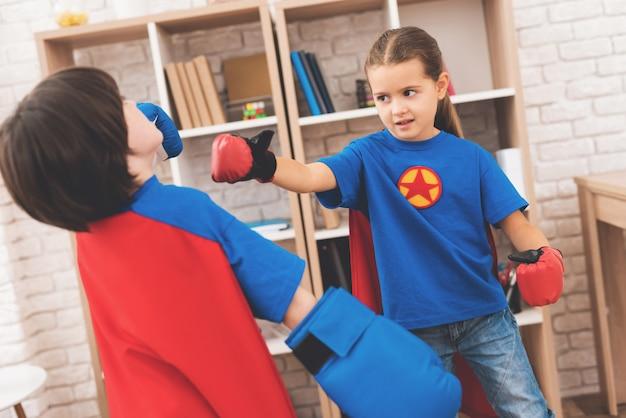 Crianças em fantasias de super-heróis lutam em casa.