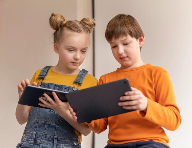Crianças em filmagem média aprendendo com dispositivos