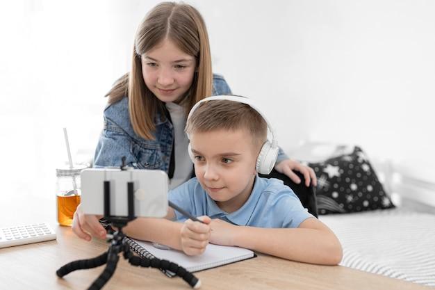 Crianças em filmagem média olhando para smartphone