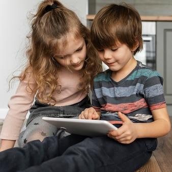 Crianças em filmagem média olhando para um tablet