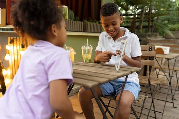 Crianças em filmagem média sentadas à mesa com um tablet