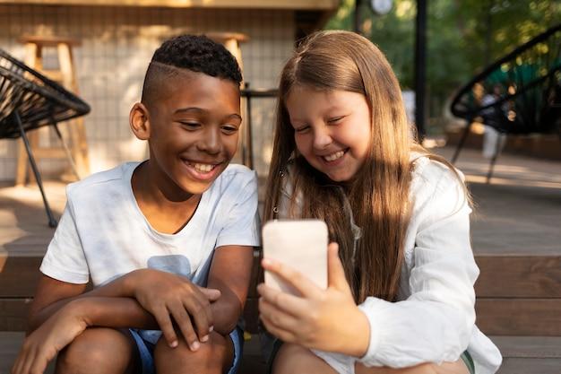 Crianças em filmagem média tirando selfie