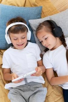 Crianças em filmagens médias com laptop e fones de ouvido